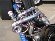 A Pair of turbochargers mounted to an Inline 6 engine in a dragster.
